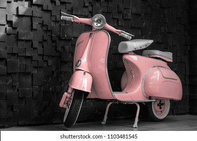 Phuket, Thailand - June 1, 2018: 1964 vintage pastel pink Vespa parking at the black wooden wall of the restaurant. The iconic Italian designed scooter.
