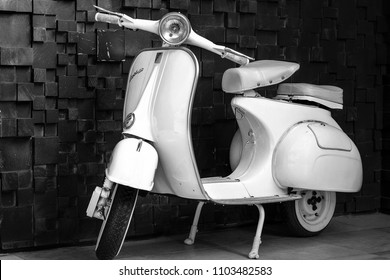 Phuket, Thailand - June 1, 2018: 1964 vintage pearl white Vespa parking at the black wooden wall of the restaurant. The iconic Italian designed scooter. Black and White.