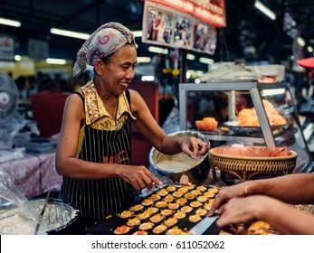 Phuket, Thailand - June 20, 2016: The seller with food in the market on the street Thalang on June 20, 2016 in Phuket, Thailand