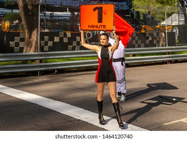 Phuket, Thailand - June 2017: Toyota motorsport beautiful sexy grid girl with red flag. Woman in a short dress auto racing in Toyota Fast Fun Fest. Sexy model young girl