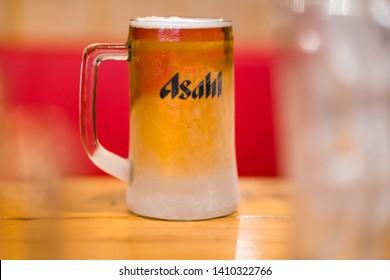 PHUKET, THAILAND - MAR 29, 2019: chilled asahi beer mug with foam on table, asahi is one of favorite japan beer