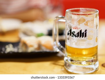 PHUKET, THAILAND - MAR 8, 2019: chilled asahi beer mug with foam and blurred japanese food, asahi is one of favorite japan beer
