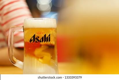 PHUKET, THAILAND - MAR 8, 2019: chilled asahi beer mug with foam on table with light bokeh, asahi is one of favorite japan beer
