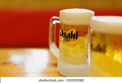 PHUKET, THAILAND - MAR 8, 2019: chilled asahi beer mug with foam on table, asahi is one of favorite japan beer