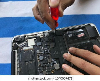 Phuket, Thailand – March 15, 2019: user of Apple Mac book laptop is showing how to change battery by herself at home