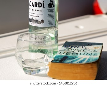 Phuket, Thailand - March 2019: Vacation on the sailing yacht. Bottle of bacardi white rum, glass and book Angels and Demons of Dan Brown. Happy vacation on luxury yacht in Andaman sea of Indian ocean