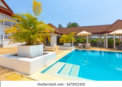 Phuket, Thailand - March 2020: Pool of The Sands Condominium on Nai Harn beach, Phuket island, Thailand. Turquoise pool water in a luxury resort in the tropics. Sun beds and umbrellas near water