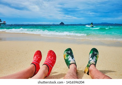 PHUKET, THAILAND - MAY 1, 2019: The coast of Khai Nok island with a view on the female and mail lying legs in water shoes, on May 1 in Phuket