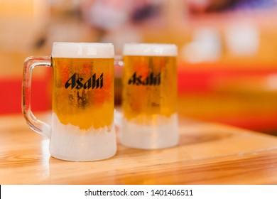 PHUKET, THAILAND - MAY 10, 2019: chilled asahi beer mug with foam on table, asahi is one of favorite japan beer