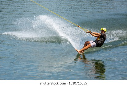 Phuket, Thailand - Nov 2014: Wakeboard training in Thailand. Jumping on the board with lots of splashes. Man in a helmet and a life jacket trains on an artificial pond in Phuket on a wakeboard.