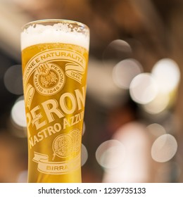 PHUKET, THAILAND - NOV 21, 2018: glass of cold peroni beer on table with light bokeh, peroni is number one lager brand in Italy