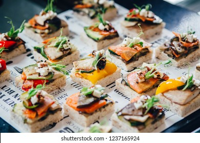Phuket, Thailand – November 21, 2018: Mini tapas with an Asian twist isolated on food tags typography textured background served at coffee break in the hotel.