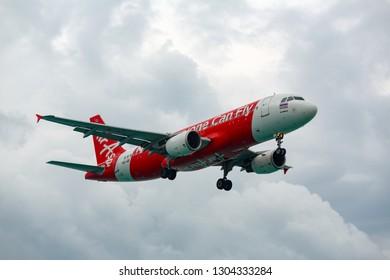 PHUKET, THAILAND - NOVEMBER 28, 2016: Airbus A320-216, HS-ABI of AirAsia flies in a stormy dark sky