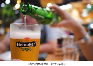 PHUKET, THAILAND - OCT 1, 2018: heineken beer logo on glass, beer from Netherlands, blurred man as background