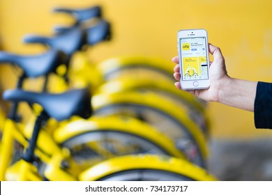 "PHUKET, THAILAND - OCT 14, 2017: user of bike sharing project, ""scan to go"", use ofo app via iPhone SE, this project supported by Obike and Ofo, bicycle rental companies, phuket, Thailand"