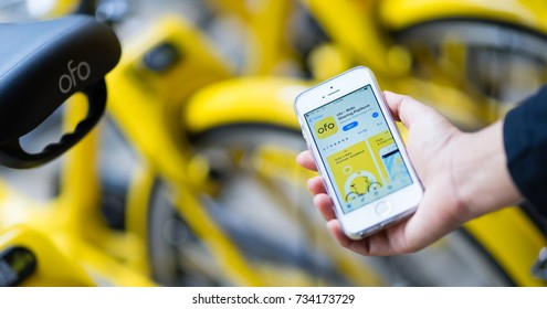 """PHUKET, THAILAND - OCT 14, 2017: user of bike sharing project, """"scan to go"""", use ofo app via iPhone SE, this project supported by Obike and Ofo, bicycle rental companies, phuket, Thailand"""