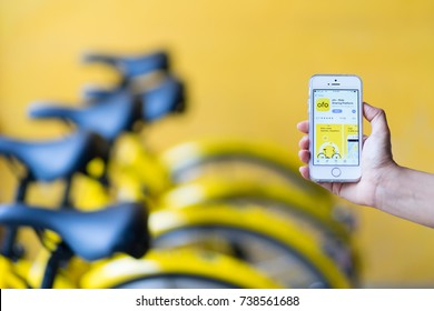 PHUKET, THAILAND - OCT 14, 2017: user of bike sharing project, scan to go, use ofo app via iPhone SE, this project supported by Obike and Ofo, bicycle rental companies, phuket, Thailand