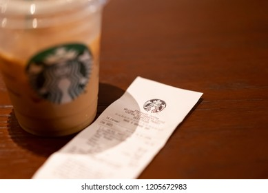 PHUKET, THAILAND - OCT 16, 2018: reciept of starbucks coffee and blurred plastic cup as background, starbucks is well known global coffee company