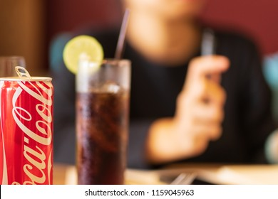 PHUKET, THAILAND - OCT 24, 2017: can of coca-cola, on table in restaurant, blurred people as background