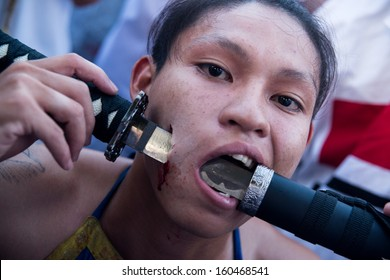 PHUKET, THAILAND - OCTOBER 10: An unidentified devotee of a Chinese shrine gets pierced on his cheeks to take part in the 2013 Vegetarian Festival on October 10, 2013 in Phuket, Thailand