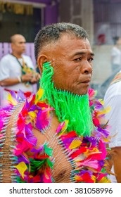 PHUKET, THAILAND - OCTOBER 17, 2015: Devotee with several needles pierced waits for the procession to start at the Vegetarian Festival.
