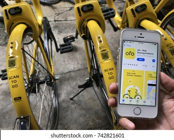"""phuket, thailand - october 24, 2017: user of bike sharing project """"scan to go"""" which is managed by thai government, using ofo application via iphone se"""