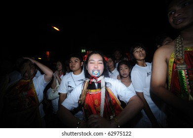 PHUKET, THAILAND - OCTOBER 7 : the ninth lunar month of the Chinese calendar starts  the Vegetarian Festival October 7, 2010 in Phuket, Thailand. Participants in the festival perform acts of body piercing as a means of shifting evil spirits from individua