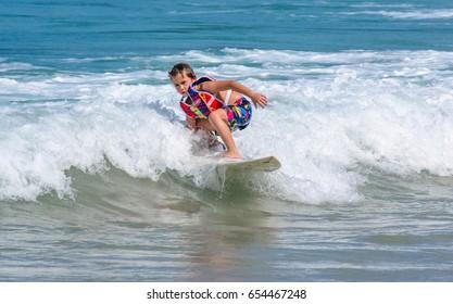 PHUKET, THAILAND - SEPTEMBER 21: A little Western boy practicing surfing in Kata beach -Phuket island, Thailand on September 21,2014. Kata beach is the paradise for surfer on Monsoon season.
