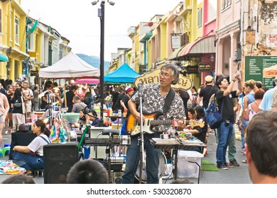 PHUKET, THAILAND SEPTEMBER 27: Street artist musician entertains tourists at the walking street among old building Chino Portuguese style on street of Phuket town, Thailand on September 27, 2016.