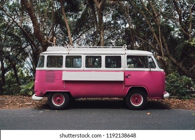 Phuket, Thailand – September 29, 2018: Vintage cerise pink Volkswagen van parking on the beach road with tropical trees in the background.