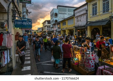 Phuket Town, Phuket / Thailand - 2/4/2017: Night market in a street of Phuket Old Town, Thailand. People are browsing stalls selling products and food right before sunset.