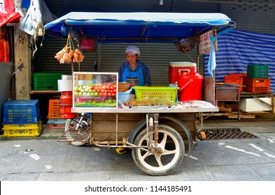 Phuket Town, Thailand - April 29, 2017: Thai woman behind her street food push cart on Bangkok Soi 4 next to Ranong Road.