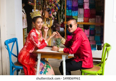 PHUKET TOWN, THAILAND - JANUARY 4. 2019: Photo shooting of young Thai couple in traditional dress sitting at table on chairs holding hands in front of gift shop