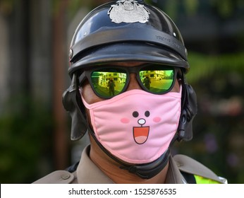 PHUKET TOWN, THAILAND - OCT 4, 2019: Royal Thai motorcycle police officer wears mirrored sunglasses and a funny protective face mask in pink and poses for the camera, on Oct 4, 2019.