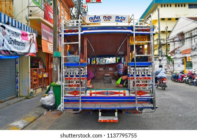 Phuket Town, Thailand - October 16, 2014: Rear view of the songthaew doing the Phuket to Karon beach line, parked at the terminus in Ranong Road, with Thai people inside waiting for it to leave.