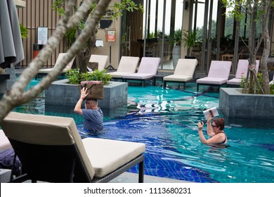 Phuket/Thailand - 14 June, 2018: Tourists carrying their belongings on their head in a swimming pool.