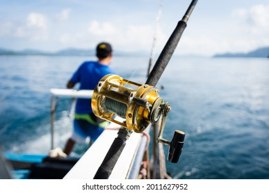 Phuket,Thailand- June 22, 2021:Fishing reels and rods reels for big game fishing trolling tuna.blue sky and blue water.Andaman sea fishing, Phuket, Thailand.Copy space and text Space.