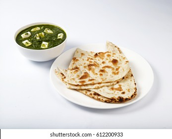 phulka served in a white plate with palak(spinach) paneer gravy on white background