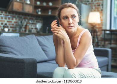 Phycological factor. Appealing mature woman looking aside and sitting on sofa