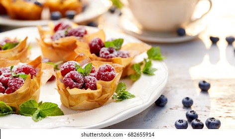 Phyllo cups with Mascarpone cheese filling topped with fresh Raspberries and mint on a white plate.