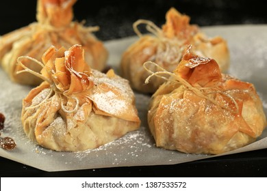 Phyllo pastry strudel with apple filling and sultana grapes, dusted with icing sugar