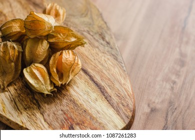 Physalis Berries with on the wooden background. Top view. Empty place for text or logo.