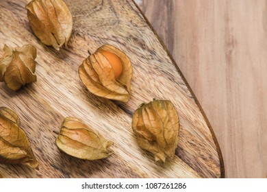 Physalis Berries with on the wooden background. Empty place for text or logo.
