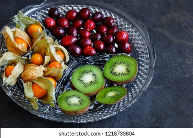 Physalis fruit - Cape gooseberries with cranberries and kiwi on cut glass platter on slate background - with copy space