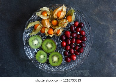 Physalis fruit - Cape gooseberries with cranberries and kiwi on cut glass platter on slate background - centered