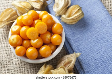 Physalis fruit with one cut in half in bowl on blue napkin and burlap.
