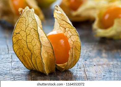 Physalis fruit (Physalis Peruviana) with husk on wooden background - closeup