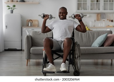 Physical activities for disabled people. Handicapped black man in wheelchair make rehabilitation exercises with dumbbells at home. Impaired guy working out with weights indoors, raises dumbbells