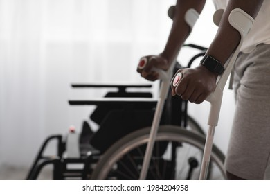 Physical activity and training to recover from injury and illness. Adult african american man disabled with crutches walks near wheelchair on large window background in interior, cropped, close up