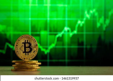 physical bitcoin standing at a wood table in front of a Green graph. Bitcoin Bull Market concept.
